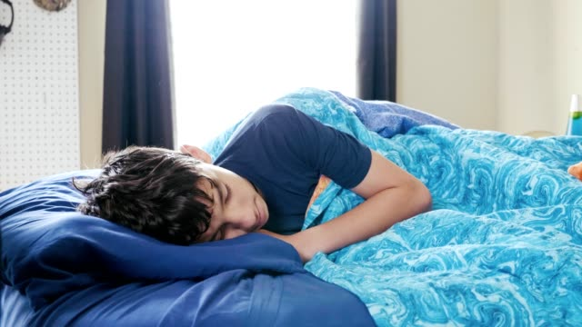 sick teenage boy sleeps in his bed during the day - teenage boys stock videos & royalty-free footage