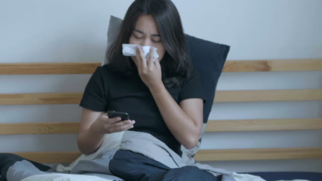 sick woman blowing nose and working - illness stock videos & royalty-free footage