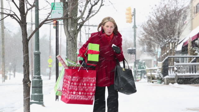 WS PAN Sick Woman Blowing Nose in Snow, Holding Christmas Presents on City Street / Richmond, Virginia, United States