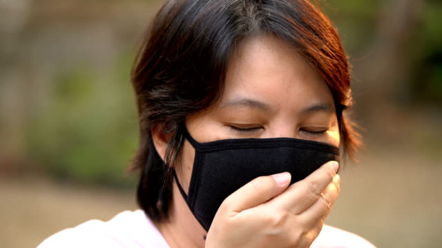sick woman coughing under air pollution mask in front view - pollution mask stock videos and b-roll footage