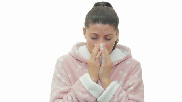 Sick woman in bathrobe coughing and blowing nose.