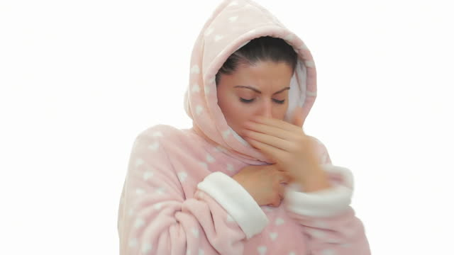 Sick woman in bathrobe coughing.