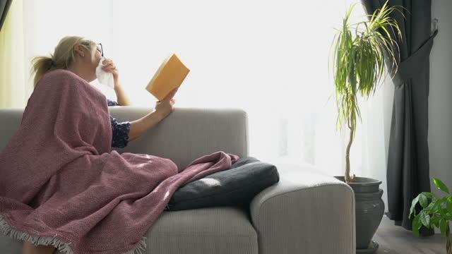 vídeos de stock e filmes b-roll de sick woman reading book at home. - 40 44 anos