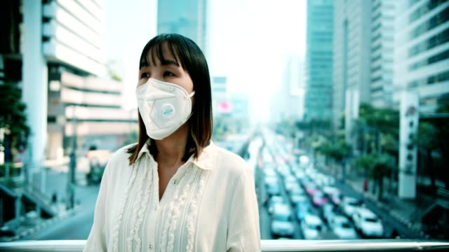sick woman with protective mask coughing while standing outdoor - pollution mask stock videos & royalty-free footage