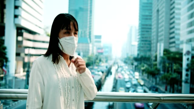 Sick woman with protective mask coughing while standing outdoor
