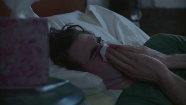 CU Sick young man in bed taking tissue from side table and blowing his nose / Brooklyn, New York City, New York, USA