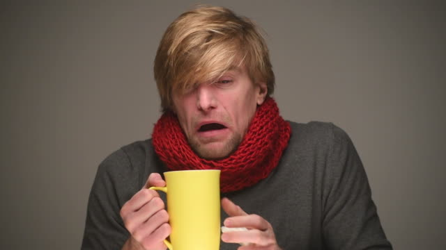 sick young man sneezes