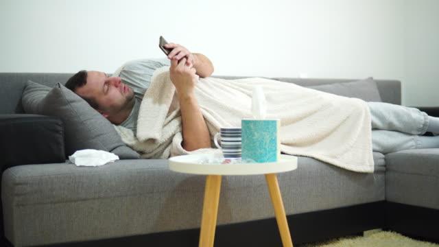 vídeos y material grabado en eventos de stock de joven enfermo que sufre de gripe en casa - pijama