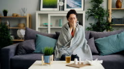 Sick young woman coughing drinking medicine sitting on couch at home