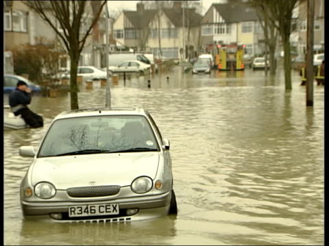 sidcup street flooded by burst water main; itn england: kent: bexley: sidcup: ext man carrying his son thru flood water as boy wearing scuba gear... - tucker stock videos & royalty-free footage