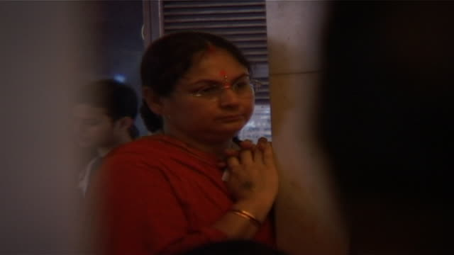 siddhivinayak temple. view of a hindu woman standing in contemplation at the shrine of ganesha, the god of transitions. twenty five thousand people... - dhoti video stock e b–roll