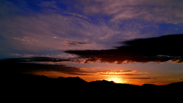 Side aerial point of view wide shot sunset and clouds over mountains / El Paso, Texas