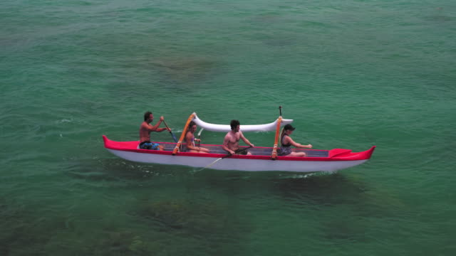 side aerial view of four people paddling in outrigger canoe - タートル湾点の映像素材/bロール