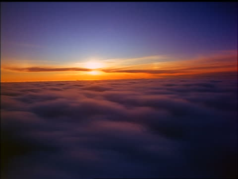 side airplane point of view over sea of clouds at sunset / starts descending into clouds - bewegliches hintergrundbild stock-videos und b-roll-filmmaterial