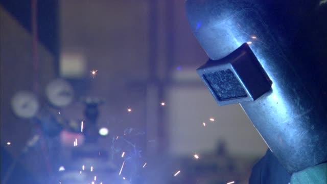 side angle, ironworker/ steelworker looking downward, welding- light from welding machine illuminating helmet & sparks shooting up- rack focus on... - welding helmet stock videos & royalty-free footage