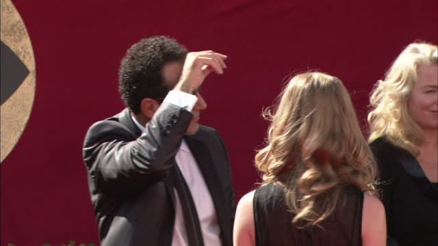 side angle MCU Tony Shalhoub wiping sweat from forehead and posing for picture with woman on red carpet as Patricia Rozema stands nearby watching