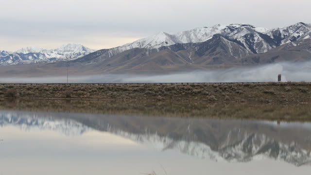 Side angle of I-80 in Utah with a mountain and mist in background and reflection on water in foreground