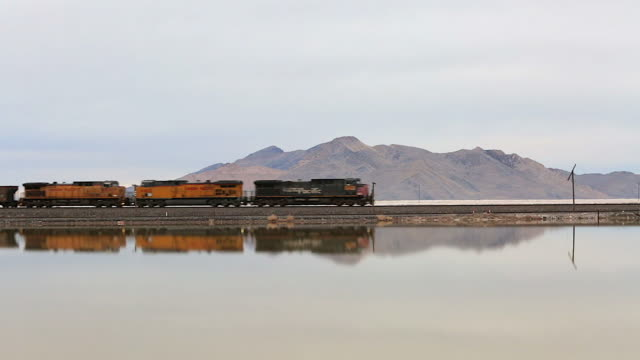 side angle of train tracks on the great salt lake as a train cuts into frame - cargo train stock videos & royalty-free footage
