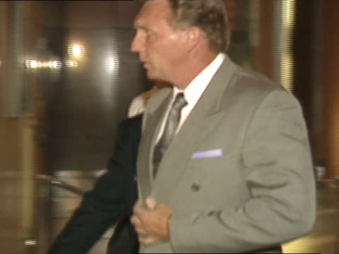 side angle ms pan with robert bobby carradine as he walks through lobby of theater with two male friends - 1991 stock videos and b-roll footage