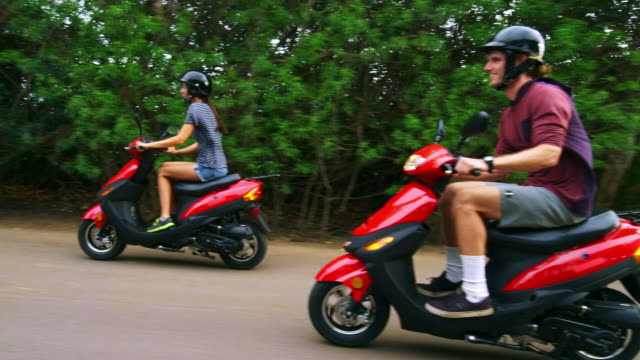 side angle view of couple on mopeds - moped stock videos and b-roll footage