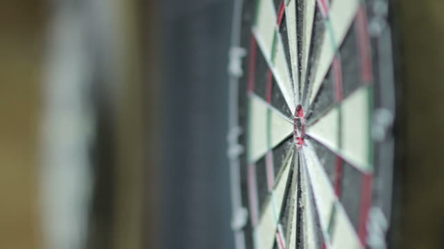 side angle view of darts being thrown at a dart board with focus on the board - dart board stock videos & royalty-free footage