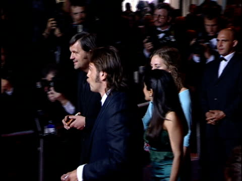 side/ back view Emir Kusturica Salma Hayek and Javier Bardem walking along red carpet stopping to pose for paparazzi