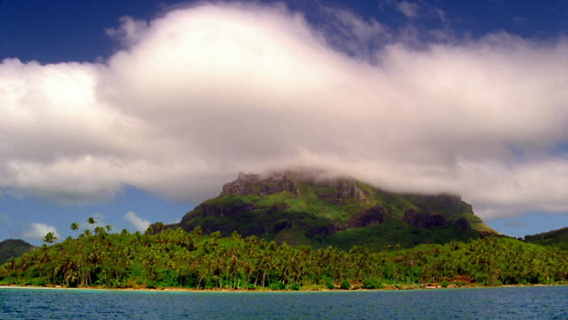 Side boat point of view low clouds hovering over rocky island / Bora Bora, French Polynesia, South Pacific