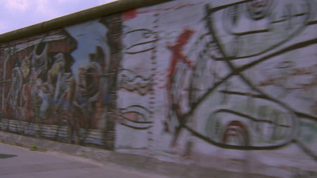 side car point of view along painted sections of berlin wall / germany - muro di recinzione video stock e b–roll