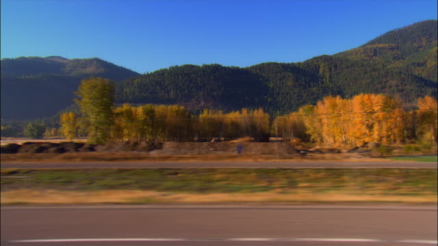 vídeos de stock, filmes e b-roll de side car point of view driving along highway 10 south of missoula, montana on clear day - side view