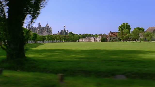 Side car point of view of Chateau Chambord and grounds / people walking in the park / France