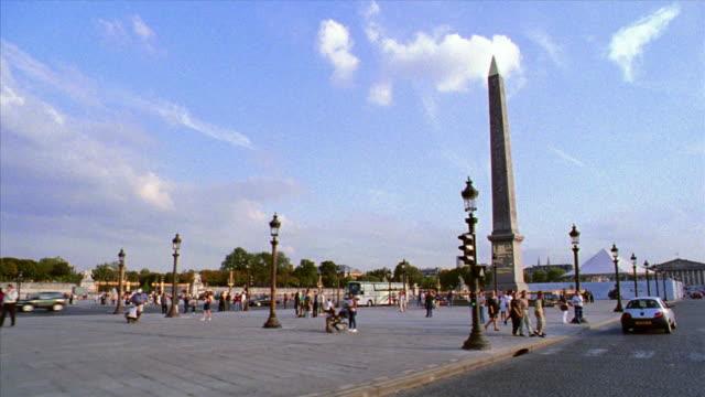 Side car point of view on street through Place de la Concorde with people on sidewalk / tilt up Luxor obelisk / Paris