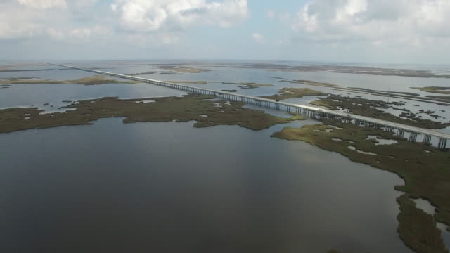 Side flight near causeway long endless bridge - Drone Aerial 4K Lake Pontchartrain CausewayGrand Isle Louisiana coast Mississippi river bridge and barge everglades, gulf delta, with wildlife 4K Transportation