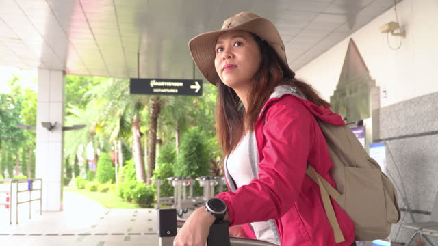 side head shot view: solo beautiful asian woman, a traveler with long black hair, hat, shoulder bag, and luggage on pushcart waiting on airport terminal to looking taxi, transportation to explore the new journey. - shoulder bag stock videos & royalty-free footage