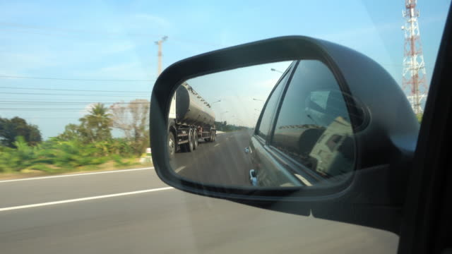 4K : Side mirror view car travel on road