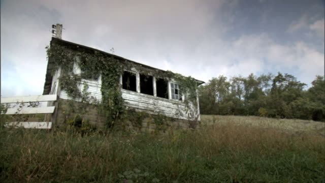 stockvideo's en b-roll-footage met side of abandoned dilapidated barn or small house w/ weeds growing around structure some broken windows grass field trees bg pa rural country... - verlaten slechte staat