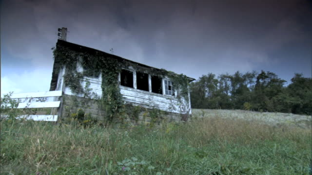 stockvideo's en b-roll-footage met side of abandoned dilapidated barn or small house w/ weeds growing around structure some broken windows grass field trees bg cloudy sky pa rural... - verlaten slechte staat