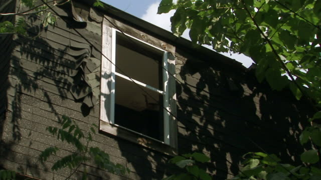 vidéos et rushes de side of house w/ newer window framed in untreated wood inexpensive tar paper shingles bunching up near window frame low budget cheap repairs... - maryland état