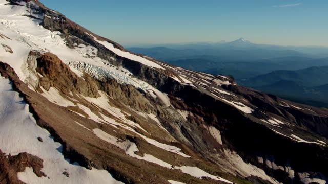 MS AERIAL Side of Mt Hood pan up to peak / Oregon, United States
