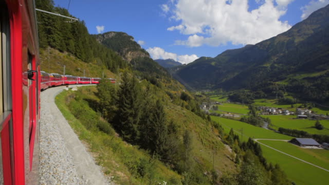 stockvideo's en b-roll-footage met side of red train from window with verdant valley and scattered houses - swiss alps, switzerland - train vehicle