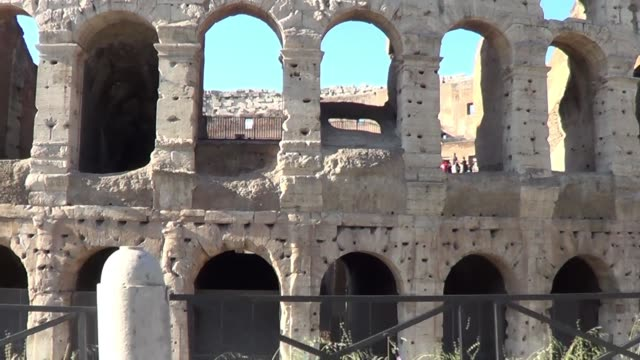 side of the colosseum filmed from moving car in rome italy surrounded by tourists - amphitheatre stock videos & royalty-free footage