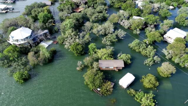 側面パン空中ドローン図洪水避難、洪水と自然災害、家に殺到した葉と水の下でです。気候変動 - ダメージ点の映像素材/bロール