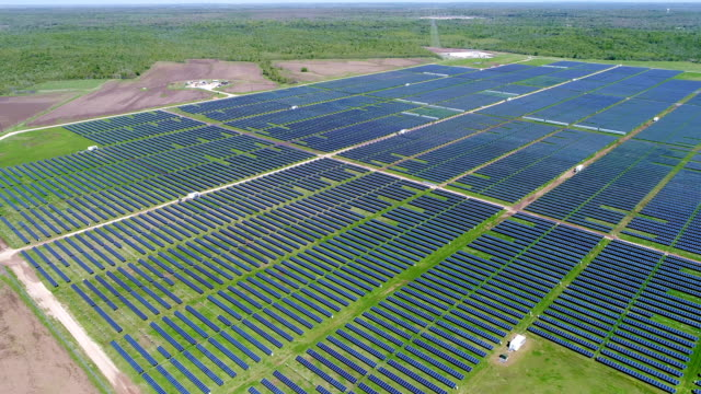 sida pan högt upp hela solpanelen array på solpanel kraftverket ger ren förnybar energi att hjälpa kampen mot klimatförändringarna och skapa arbetstillfällen - ansvarsfullt företagande bildbanksvideor och videomaterial från bakom kulisserna