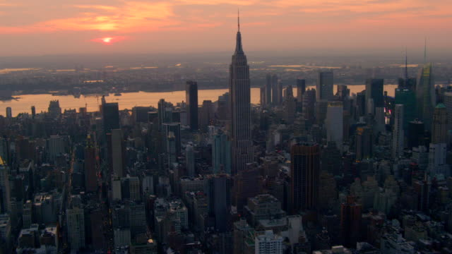aerial side pov past empire state building and midtown manhattan at sunset - metlife hochhaus stock-videos und b-roll-filmmaterial