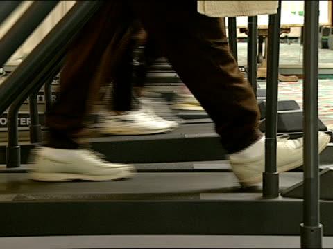 people's feet, legs walking on treadmill, row of treadmills in gym. people legs walking in row. - trainingsmaschine stock-videos und b-roll-filmmaterial