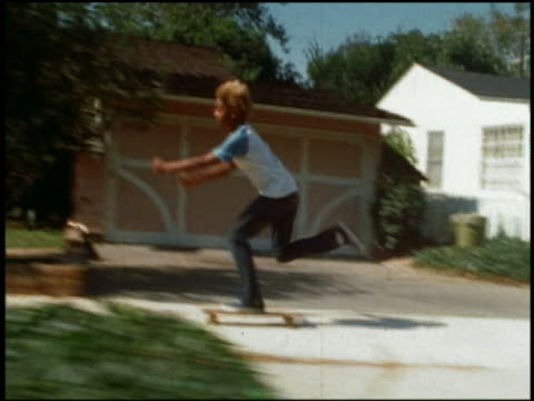 stockvideo's en b-roll-footage met 1977 side point of view boy skateboarding along suburban sidewalk / brentwood, california, usa - 1977