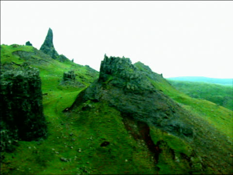 AERIAL side point of view grassy mountains with jagged rocks / The Storr, Isle of Skye, Scotland