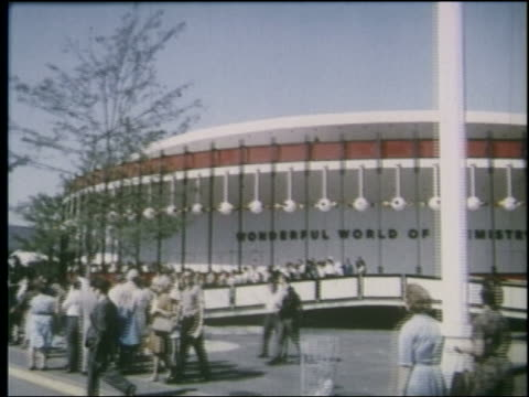 1964 side point of view past crowd in front of wonderful world of chemistry pavilion at ny world's fair - 1964年点の映像素材/bロール