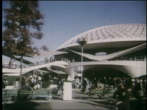 1964 side point of view past exterior of round theater with people in front at ny world's fair - 1964年点の映像素材/bロール