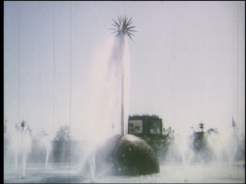 1964 side point of view past fountain with sculpture in center at ny world's fair - esposizione universale di new york video stock e b–roll