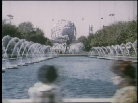 vídeos de stock, filmes e b-roll de side point of view past fountains in pond with unisphere in background at ny world's fair - world's fair de nova york